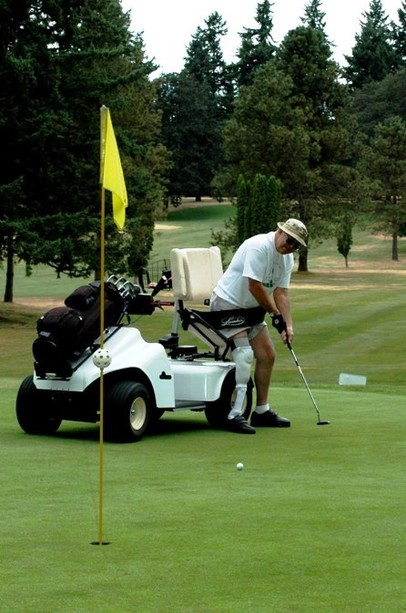 Disabled man using Paragolfer putts on green